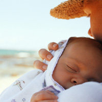 Mom holding baby on the beach