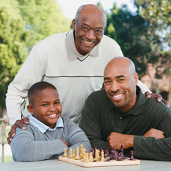 Single dad with his son and father playing chess